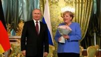 Rus lider Putin Merkel'le görüşmesine çiçekle geldi!